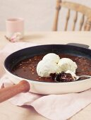 Schokoladenkuchen mit Vanilleeis in einer Pfanne