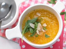 Carrot and potato cream soup with rocket and almond flakes