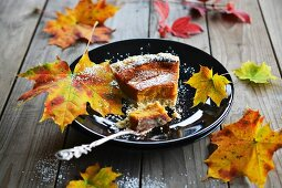 Sweet potato cake decorated with autumn leaves on a plate with a cake fork