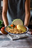 A woman holding a bowl of chickpeas, potatos, carrots and cabbage (ingredients for Cocido madrileno - a Spanish stew)