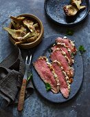 Low-cooked roast beef with a feta and almond crust and artichokes (low carb)