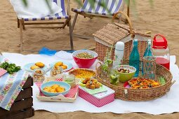 A picnic on a sandy beach with various nibbles and drinks