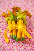 A bunch of yellow courgettes with flowers tied together with a ribbon on a floral tablecloth