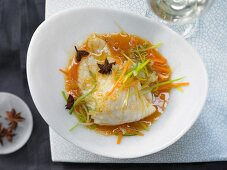 Steamed wolf fish fillet with julienne vegetables and a carrot and orange sauce with star anise