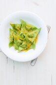 Green duck ravioli with orange sauce