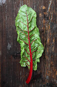A chard leaf on a wooden surface