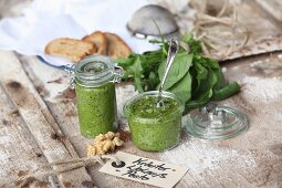 Herb and walnut pesto in glass jars