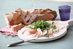 Turnip carpaccio with ham, mushrooms and arugula, served with French bread