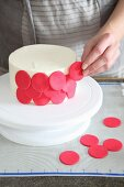 A cake being decorated with red marzipan circles