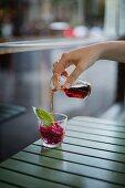Aperitif-Szene: Hand giesst Kräuterbitter auf Granatapfel-Granita im Glas