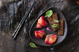 Sliced salmon filet, salted with beetroot juice, served on whole wheat toasts with salad leaves