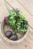 Fresh figs and herbs in a wooden bowl