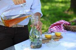 Homemade lemonade with apple juice, wild plants and lemons