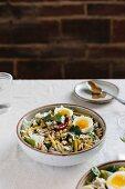 Knuspriges Gemüse mit gekochtem Ei und warmer Erdnusssauce in einer Schüssel