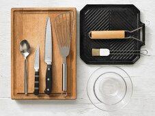 Various kitchen utensils: grill pan, glass bowls, spatula, knives, spoon