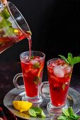 Pouring the Pomegranate Mojito in the tall glass