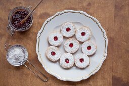 Spitzbuben (jam cookies) on a plate with jam and powdered sugar