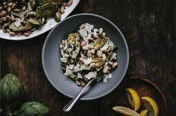 A bowl of braised baby artichoke salad with white beans and shaved manchego