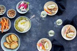 Roasted Anaheim Pepper Manchego Pesto with crostini, carrot sticks, radishes, raw almonds and walnuts in ceramic bowls