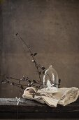Small china bird under glass cover and branches on white tablecloth