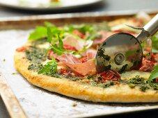 Pizza with parma ham, rocket and pesto