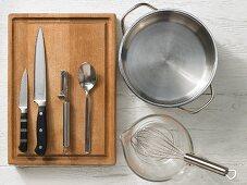 Various kitchen utensils: pot, measuring cups, whisk, knives, peeler