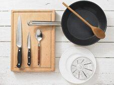 Various kitchen utensils: pan, knife, spoon, measuring cup