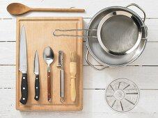 Various kitchen utensils: pot, sieve, measuring cup, knives, spoon, pastry brush, peeler