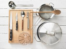 Various kitchen utensils: pot, strainer, soup ladle, measuring cup, knives