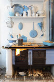 Fire in wood-fired cooker and enamel kitchen utensils