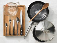 Various kitchen utensils: pot, pan, measuring cup, knives, spoons