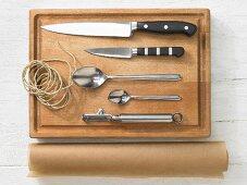 Various kitchen utensils: knives, spoons, peeler, brown string, baking paper