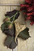 Decorative hay heart and 'maiden in the green' flowers on a rustic wooden background