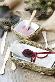 Rustic table decoration with hay trays, wooden cutlery and jute table runners