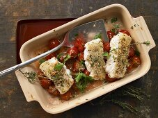 Fish fillets with an almond crust on a bed of cherry tomatoes