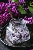 Square glass jar of lilac flowers in sugar, silver spoon and lilac branch on vintage tray