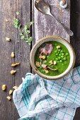 Grüne Erbsencremesuppe mit gebratenem Speck und Croutons
