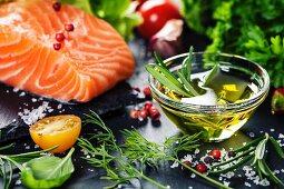 Rohes Lachsfilet mit Kräutern, Gewürzen, Gemüse und Öl im Schälchen