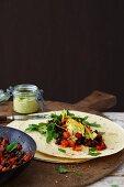 Bean burritos with rocket, cheese and a corn dip