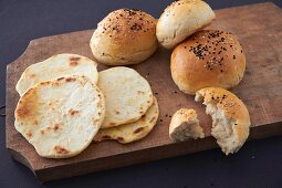 Burger buns and flatbread on a wooden board