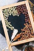 Verschiedene Kaffeebohnen mit Zucker-Sticks auf Schiefertafel
