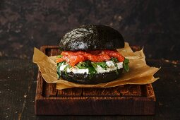 Black Salmon burger with cream cheese and arugula on dark wooden background