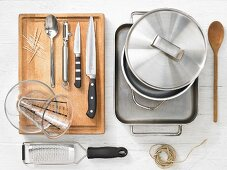 Various kitchen utensils: pot, baking dish, grater, kitchen string, measuring cup, knife, toothpick