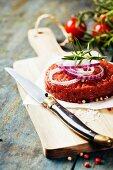 Rohes Burger-Patty mit Gewürzen, Kräutern und Zwiebeln auf Holzbrett