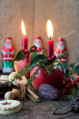 Christmas apples decorated with candles, larch cones and juniper sprigs, biscuits, chocolate Santas, dates and peanuts