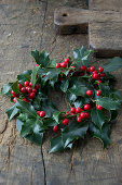 Christmas holly wreath on wooden table