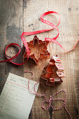 Copper christmas shaped cookie cutters on a rustic wooden surface with red Noel ribbon bakers twine and cookie recipe