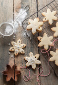 Homemade snowflake shaped Christmas biscuits cooling on a wiring rack