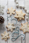 Overhead graphic shot of snowflake shaped christmas biscuits some docorated with white icing a sprinkles being threaded with blue and white bakers twine on a rustic whitewash wooden surface surrounded with Christmas decorations