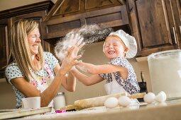Mutter und Tochter spielen mit Mehl in der Küche